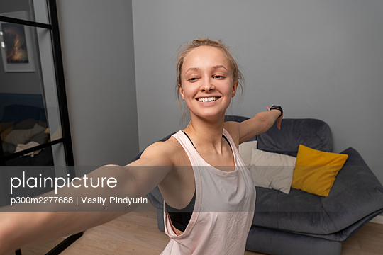 Smiling woman with arms outstretched exercising at home - p300m2277688 by Vasily Pindyurin