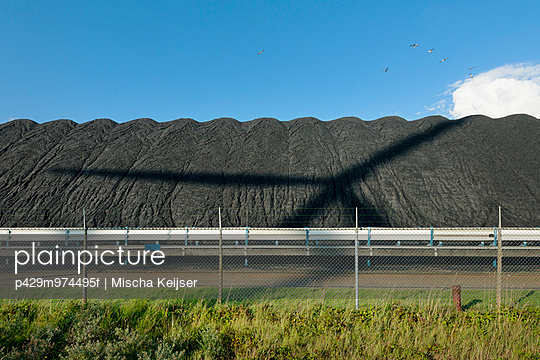 A windturbine throws its shadow over a pile of coal that waits to be burned in the nearby power station