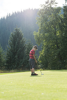 Boy playing golf in the course - p1315m1565179 by Wavebreak