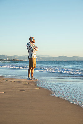 Man with headphones and sunglasses at the beach - p300m2080890 von Sebastian Kanzler