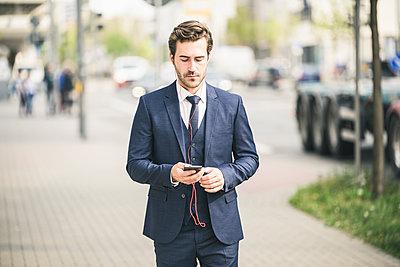 Businessman walking in the city using cell phone - p300m2104132 von Uwe Umstätter