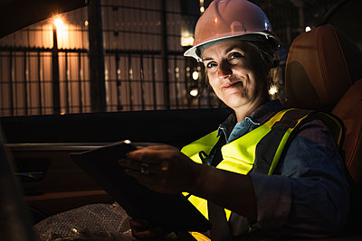 Smiling female engineer with digital tablet sitting in car - p300m2300493 by Uwe Umstätter