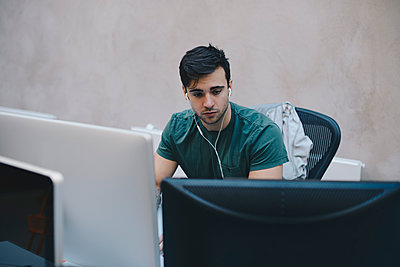 Male computer programmer using desktop PC in office - p426m1493902 by Maskot