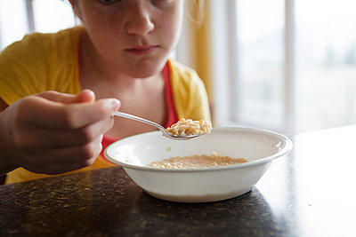 Caucasian girl eating breakfast at table - p555m1409709 by Shestock