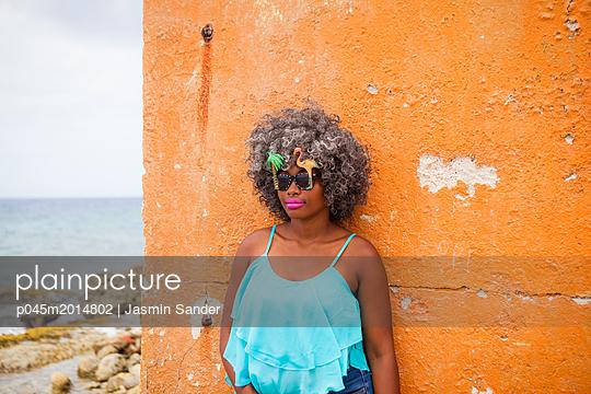 Coole junge Frau vor einer Wand - p045m2014802 von Jasmin Sander