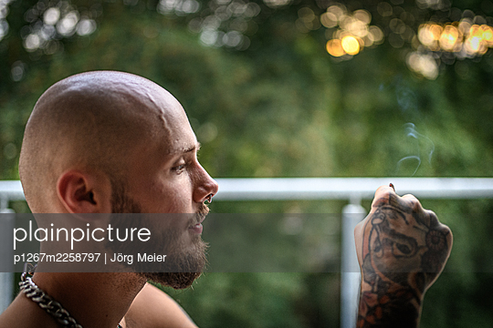 Bald man with tattoos smoking on the balcony - p1267m2258797 by Jörg Meier