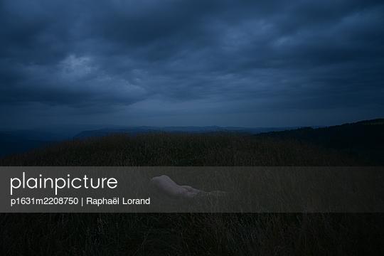 Man lying on the grass - p1631m2208750 by Raphaël Lorand