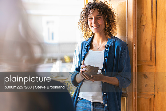 Happy curly woman looking at female friend while holding coffee mug - p300m2257230 by Steve Brookland
