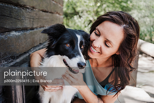 Smiling woman looking at dog while hugging by cottage in forest - p300m2293415 by Eva Blanco
