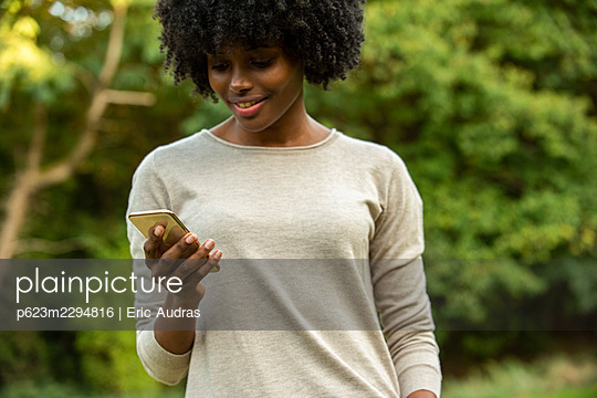 Smiling young woman using smart phone in park - p623m2294816 by Eric Audras