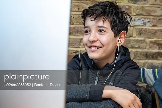 UK, Smiling boy attending online classes - p924m2283052 by Bonfanti Diego