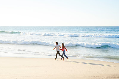 Young couple running on beach - p1124m1508607 by Willing-Holtz