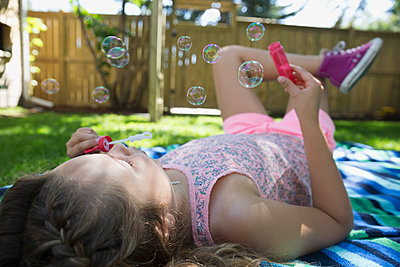 Girl laying on blanket blowing bubbles in backyard - p1192m1183942 by Hero Images