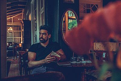 Mann sitzt lesend im Cafe - p1491m2163742 von Jessica Prautzsch