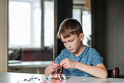 Boy assembling robot at home - p300m2170127 by Ekaterina Yakunina