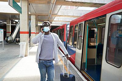 Mature businessman wearing protective face mask talking on phone at railroad station platform - p300m2241549 von Pete Muller