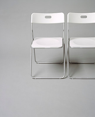 Two white folding chairs - p5250015 by Anne Deppe