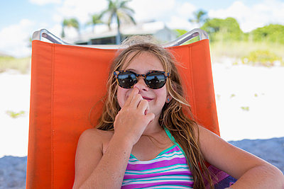 Caucasian girl picking nose on beach - p555m1411356 by Marc Romanelli