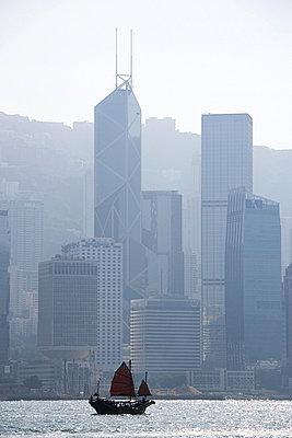 Sailboat near hong kong skyscrapers - p9247754f by Image Source