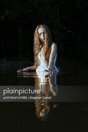 Woman in summer dress in lake - p1019m2141956 by Stephen Carroll