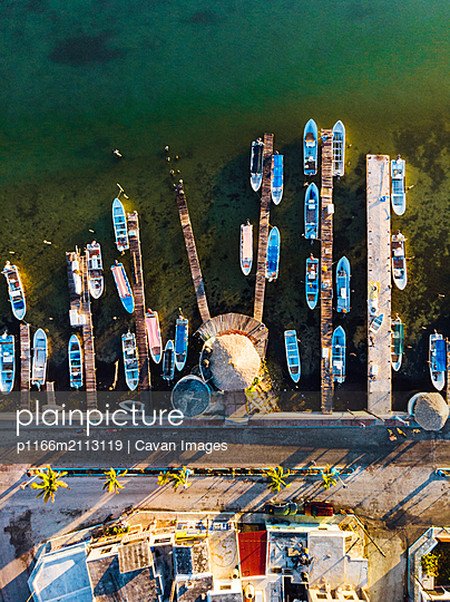 Aerial view of boats and piers in port with palm trees at sundown - p1166m2113119 by Cavan Images