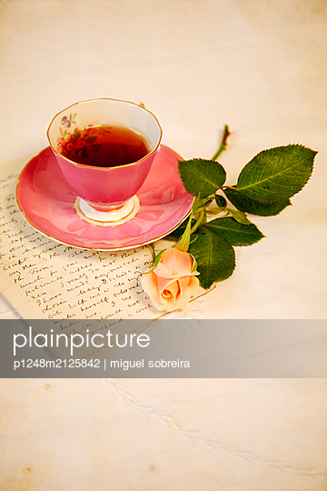 Tea Cup with Letter and Rose on Tablecloth - p1248m2125842 by miguel sobreira