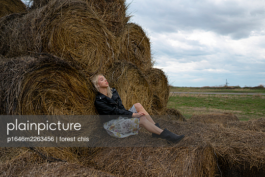Young woman on hay bales - p1646m2263456 by Slava Chistyakov