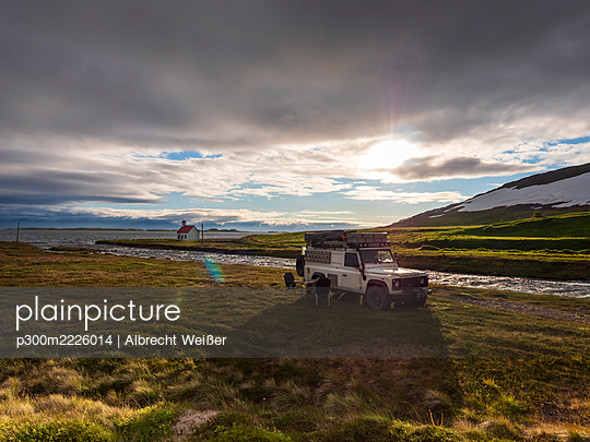 Off-road car parked in front of Icelandic river at cloudy sunset with secluded Unadsdalskirkja church in background - p300m2226014 by Albrecht Weißer