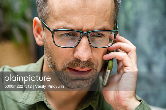Close-up of businessman talking on mobile phone at cafe - p300m2227312 by Vasily Pindyurin
