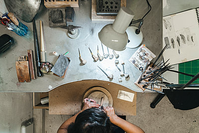 High angle view of female artisan making jewelry on wooden table in workshop - p1166m2011388 by Cavan Images