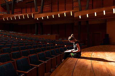 Female performer reviewing notes on stage in empty auditorium - p1192m2123236 by Hero Images