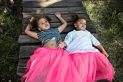 Two girls in tulle skirt lying on back - p1640m2246846 by Holly & John