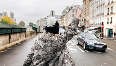 France, Paris, back view of young woman hailing a taxi - p300m1204635 by Marco Govel