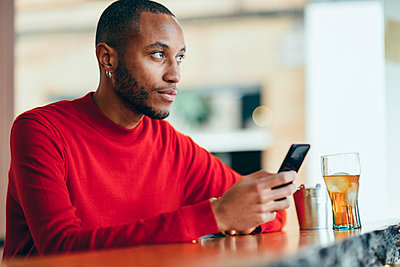 Pensive young man wearing red pullover at counter of a bar with soft drink and mobile phone - p300m2070079 by Javier Sánchez Mingorance