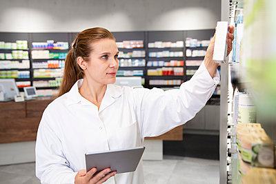 Female pharmacist with digital tablet checking medicine in store - p300m2251851 by Florian Küttler