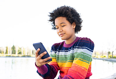 Girl using smart phone while sitting at park - p300m2252654 by Jose Carlos Ichiro