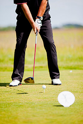 Low section of man playing golf at golf course - p426m747324f by Astrakan
