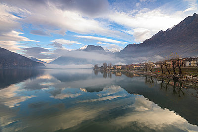Mountains and village are reflected in Lake Mezzola at dawn shrouded by mist, Verceia, Chiavenna Valley, Lombardy, Italy, Europe - p871m1498215 by Roberto Moiola