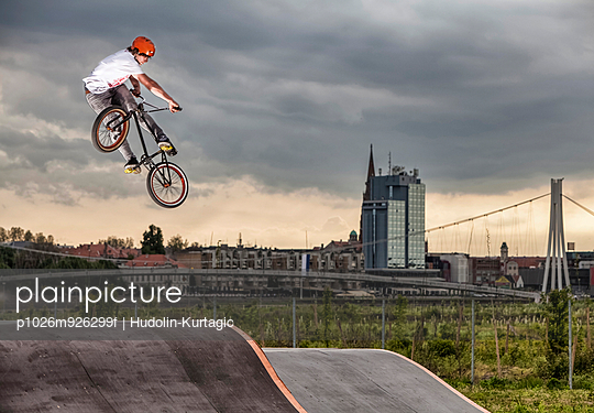 BMX biker performing a stunt against city skyline, Osijek, Croatia