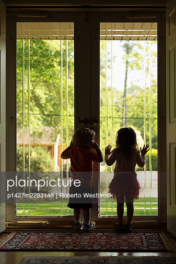 Male and female toddler friends silhouetted by patio door - p1427m2283148 by Roberto Westbrook