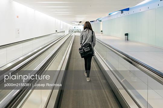 Young businesswoman on moving walkway - p300m2155381 by Josep Rovirosa