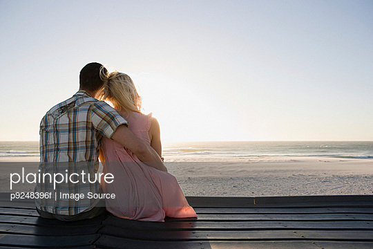 A couple sat on a pier - p9248396f by Image Source