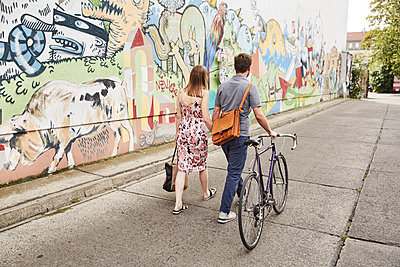 Couple with bicycle passing wall with graffiti - p300m1196904 by Sullivan