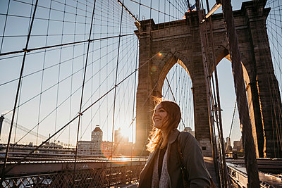 USA, New York, New York City, female tourist on Brooklyn Bridge at sunrise - p300m2081051 von letizia haessig photography