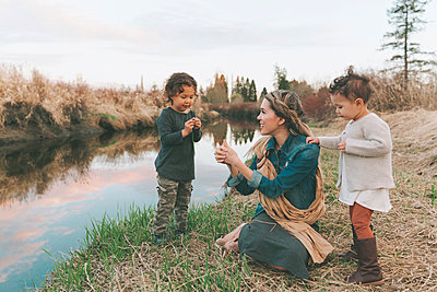 Maother and children playing with a grass blade at a river - p300m2102768 by Crystal Sing