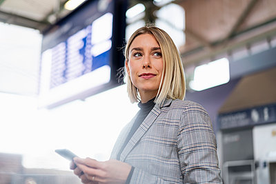 Young businesswoman with mobile phone at the train station - p300m2143482 by Daniel Ingold