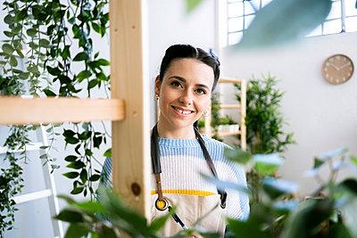 Young woman working in a gardening laboratory or plant shop - p300m2275361 von Giorgio Fochesato