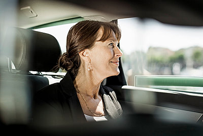 Businesswoman looking out through taxi window - p426m844658f by Maskot
