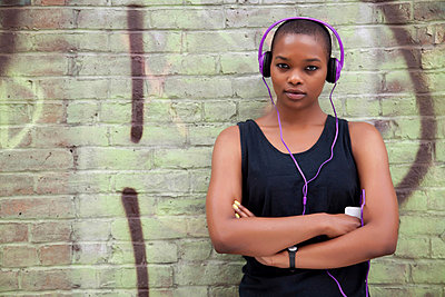 Young woman wearing headphones - p924m711110f by Camarena
