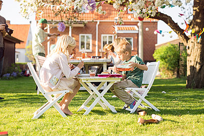 Children (4-5, 8-9) sitting at picnic table in garden - p1264m1524021 by Astrakan